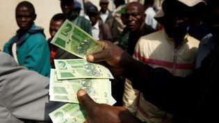 Un homme présente les nouveaux billets de 2 dollars zimbabwéens à côté de clients faisant la queue près d'une banque à Harare le 12 novembre 2019. (PHILIMON BULAWAYO / X02381)