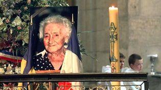 Des enfants de choeur sont assis derrière le portrait de Jeanne Calment, dans la Primatiale Sainte-Trophime, le 7 août 1997. (GEORGES GOBET / AFP POOL)