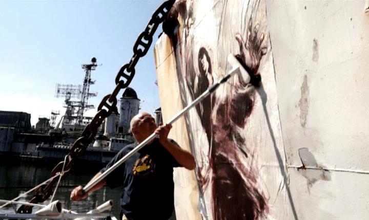 Paul Bloas colle une peinture sur une épaves de navire de guerre  (France 3 culturebox)