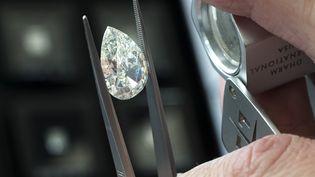 Un acheteur examine un diamant lors de la bourse aux pierres précieuses en Israël de février 2017. (JACK GUEZ / AFP)