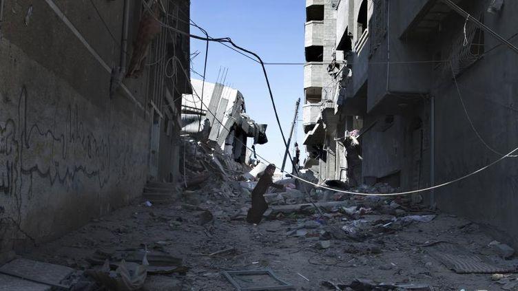 Une Palestinienne court pour tenter de se mettre à l'abri des bombes à Gaza, le 27 juillet 2014. (FINBARR O'REILLY / REUTERS)
