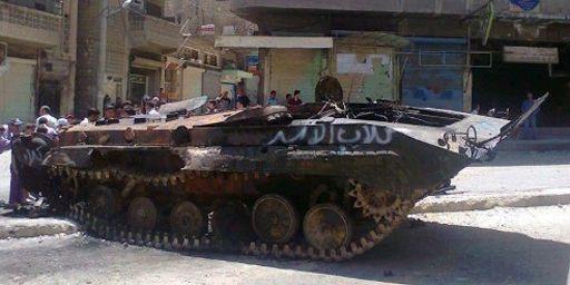 """Véhicule détruit de l'armée syrienne dans la ville d'Ariha (province d'Idlib, nord-ouest). Sur la carcasse, on peut lire le slogan """"Chiens d'Assad"""", écrit en arabe (AFP - HO - SHAAM NEWS NETWORK)"""