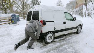 Un homme pousse sa voiture bloquée dans la neige à Saint- Etienne (Loire), le 20 novembre 2013. (PHILIPPE DESMAZES / AFP)