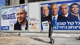 Un homme passe devant des affiches de campagne électorale portant les portraits du Premier ministre israélien Benjamin Netanyahu (à gauche), chef du parti Likoud, et du général israélien à la retraite Benny Gantz (à droite), l'un des chefs du parti politique bleu et blanc (Kahol Lavan), à Tel-Aviv le 3 avril 2019. (JACK GUEZ / AFP)