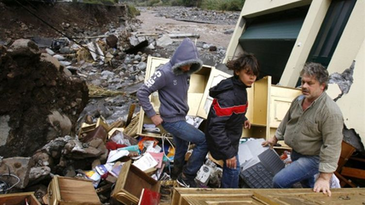 Une famille contemple les dégâts de sa maison à Funchal, capitale de l'île portugaise de Madère (AFP PHOTO - GREGORIO CUNHA)