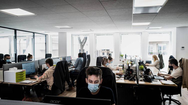 Des personnes portent des masques sur leur lieu de travail dans une entreprise lyonnaise, le 1er septembre 2020 à Lyon, le premier jour où ils sont devenusobligatoires dans les entreprises. (JEFF PACHOUD / AFP)