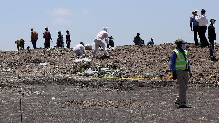 Des Ethiopiens ramassent les débris du vol d'Ethiopian Airlines, le 15 mars 2019 à Addis-Abeba (Ethiopie). (MINASSE WONDIMU HAILU / ANADOLU AGENCY / AFP)