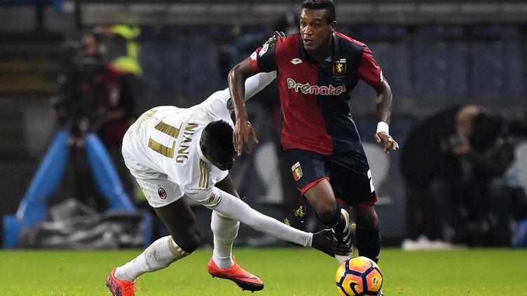 Le Milanais Niang en difficulté face au Génois Edenilson. (GIUSEPPE CACACE / AFP)