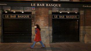 Une femme marche dans la rue à Toulouse (Haute-Garonne) et passe devant un bar fermé, alors que la ville a mis en place un couvre-feu, le 17 octobre 2020. (XAVIER DE FENOYL / MAXPPP)