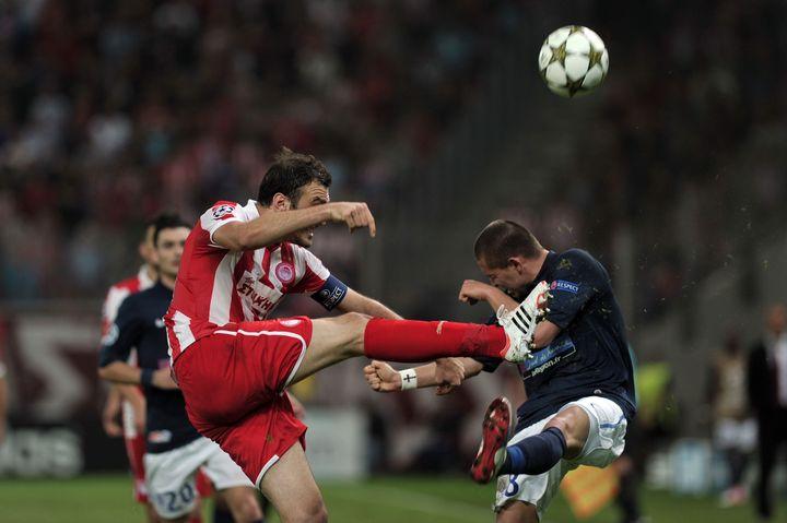 Le joueur de l'Olympiakos Vassilis Torossidis (G) à la lutte avec le joueur de Montpellier Anthony Mounier (D) lors du match Olympiakos-Montpellier, à Athènes, le 6 novembre 2012. (LOUISA GOULIAMAKI / AFP)