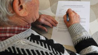 Une personne âgée remplit une attestation obligatoire nécessaire pour chaque déplacement pendant l'épidémie de coronavirus, le 18 mars 2020. (PASCAL BACHELET / BSIP / AFP)