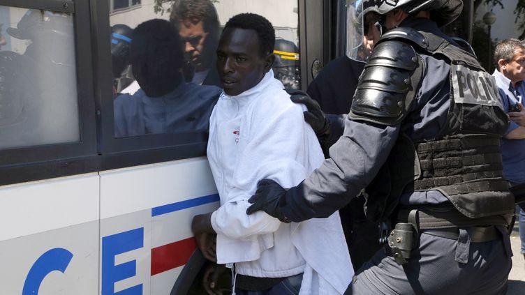 Un migrant est interpellé par un policier, à Paris, le 9 juin 2015. (FRANCOIS GUILLOT / AFP)