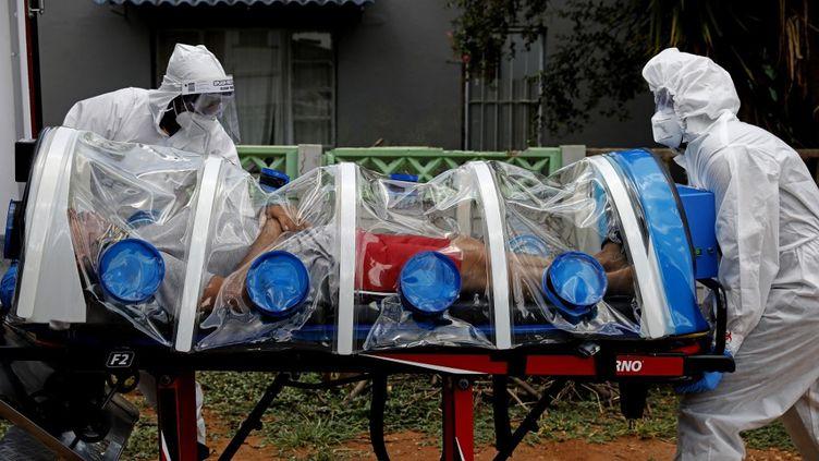Des ambulanciers poussent un homme présentant des symptômes de coronavirus à l'intérieur d'une ambulance,au nord de Pretoria, en Afrique du Sud, le 15 janvier 2021. (PHILL MAGAKOE / AFP)