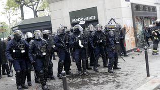 Des forces de l'ordre protègent un restaurant McDonald's saccagé par des manifestants, le 1er mai 2018 à Paris. (THOMAS SAMSON / AFP)