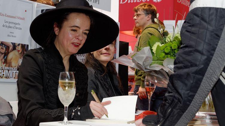 Reine du best-seller et de la dédicace, Amélie Nothomb se plie à l'exercice avec le sourire et une coupe de champagne, à Bruxelles, en Belgique, le 23 février 2014. (CITIZENSIDE/OLIVIER GOUALLEC / AFP)