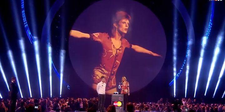 David Bowie plane sur les Brit Awards 2014, mais c'est Kate Moss qui vient recevoir son prix du Meilleur chanteur des mains de Noel Gallagher.  (Brit Awards)
