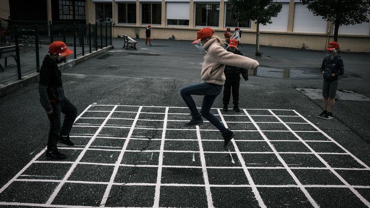 Des élèves jouent dans la cour de l'école élémentaire de La Grand-Croix (Loire), le 12 mai 2020. (JEAN-PHILIPPE KSIAZEK / AFP)
