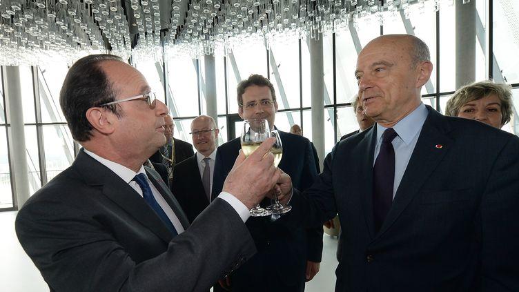 François Hollande et Alain Juppétrinquent lors del'inauguration de la Cité du vin, à Bordeaux, le 31 mai 2016. (MEHDI FEDOUACH / AFP)