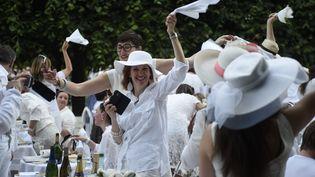 """Des participants à un """"dîner en blanc"""" font tourner les serviettes, le 11 juin 2015, dans le jardin du Palais-Royal, à Paris. (DOMINIQUE FAGET / AFP)"""