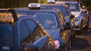 Des chauffeurs en grève s'apprêtent à passer la nuit dans leur taxi, porte Maillot, à Paris, le 28 janvier 2016. (GEOFFROY VAN DER HASSELT / AFP)