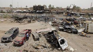 Des habitants regardent les dégâts provoqués par un attentat-suicide sur un marché de Khan Bani Saad, le 18 juillet 2015, au nord de Bagdad (Irak). (AHMED SAAD / REUTERS )