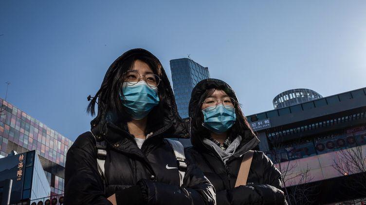 2 femmes portent un masque pour se protéger du coronavirus à Pékin (Chine), le 23 janvier 2020. (NICOLAS ASFOURI / AFP)