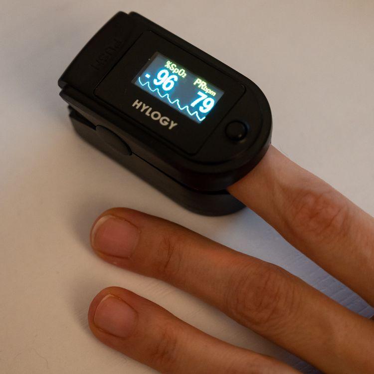 Un oxymètre indique la saturation en oxygène du sang et le rythme cardiaque d'un patient, à Paris, en décembre 2020. (RICCARDO MILANI / HANS LUCAS / AFP)
