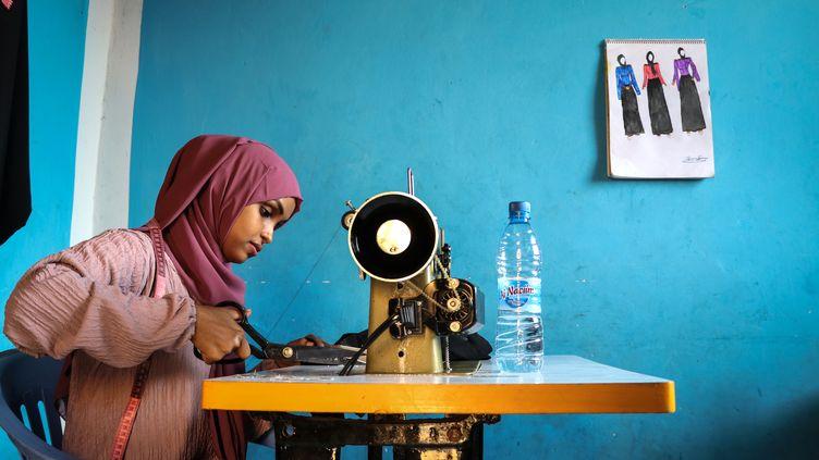Hawa Adan Hassan, étudiante de 23 ans, utilisant une machine à coudre dans son habitation de Mogadiscio. (ABDI HAJJI HUSSEIN / AFP)