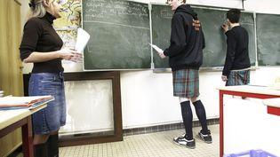 """Deux garçons en kilt travaillent avec leur professeur, le 24 mars 2006 dans une classe du lycée de Saint-Aubin-du-Cormier, où est lancée la """"Journée de la jupe"""". (FRED DUFOUR / AFP)"""