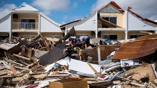 Deux hommes fouillent les ruinesd'un restaurant de la Baie-Orientale, le 10 septembre 2017, après le passage de l'ouragan Irma sur l'île de Saint-Martin. (MARTIN BUREAU / AFP)