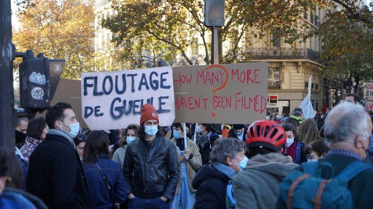 """Des personnes manifestent contre la proposition de loi de """"sécurité globale"""" et les violences policières, le 28 novembre 2020, à Paris. (MYRIAM TIRLER / HANS LUCAS / AFP)"""