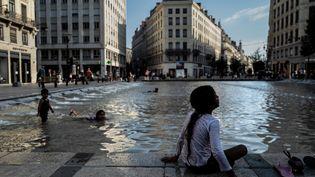 Une enfant près d'une fontaine à Lyon, le 30 juillet 2020. (JEFF PACHOUD / AFP)