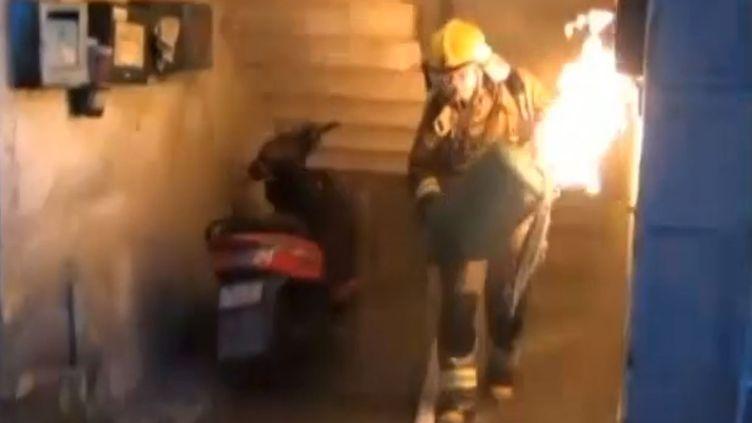 Un pompier chinois évacuant seul une bouteille de gaz en flamme à Lishui (Chine), le 16 avril 2015. (APTN / ABC7)