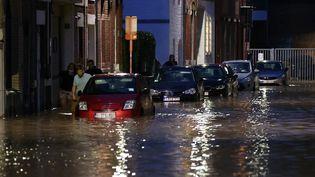 Des personnes marchentdans les rues inondées de Namur, en Belgique, le 24 juillet 2021. (DURSUN AYDEMIR / ANADOLU AGENCY / AFP)