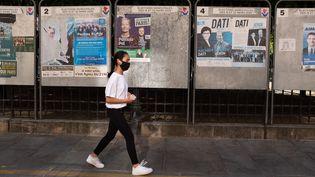 Une passante devant des panneaux électoraux à Paris, le 15 mars 2020. (LAURENCE KOURCIA / HANS LUCAS / AFP)