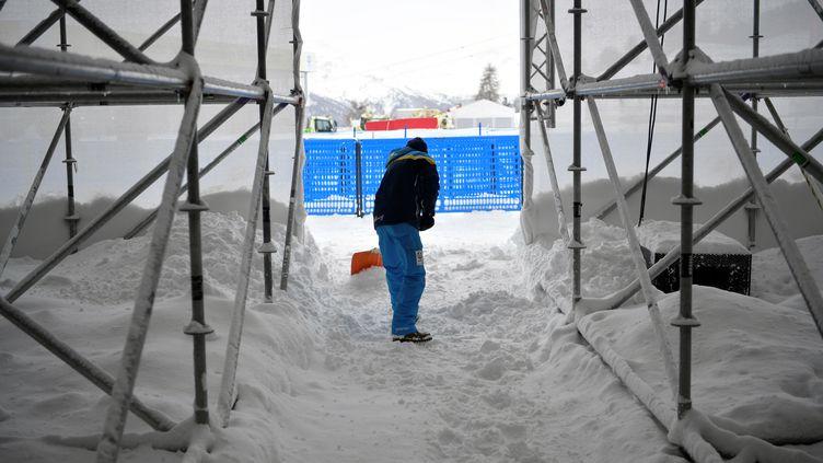 La neige est tombée abondamment et le vent complique le travail de déblayage. Les entraînements sont annulés. (FABRICE COFFRINI / AFP)