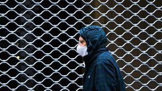 Un homme passant devant un commerce fermé, à Clermont-Ferrand, le 2 mai 2020. (RICHARD BRUNEL / MAXPPP)