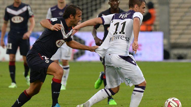 Marc Planus (Bordeaux) tente de retenir Aleksander Pesic (Toulouse) (MEHDI FEDOUACH / AFP)