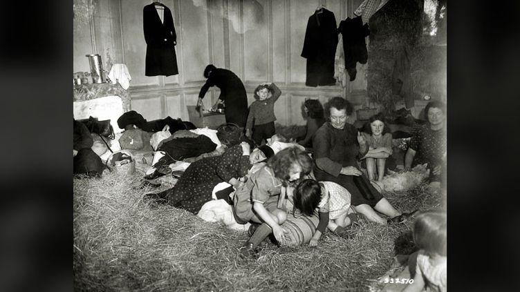 Des femmes et des enfants réfugiés dans une maison le 7 juillet 1944 dans la région de Vire (Normandie). (HULTON ARCHIVE / GALERIE BILDERWELT VIA GETTY IMAGES)