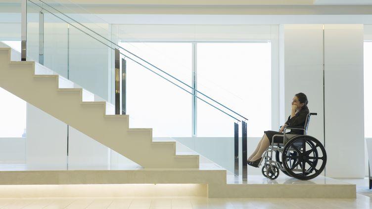 Une femme handicapée regarde les escaliers non équipés d'une rampe pouvant lui permettre de monter. (HUNTSTOCK / GETTY IMAGES )