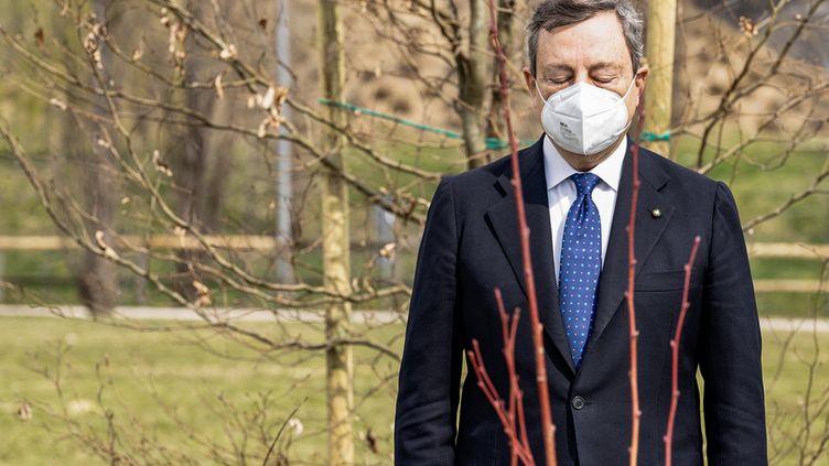 """Le Premier ministre italien Mario Draghi se recueille lors de l'inauguration du """"Bois de la mémoire"""" en mémoire aux victimes du Covid-19, le 18 mars 2021 à Bergame (Italie). (HANDOUT / PALAZZO CHIGI PRESS OFFICE)"""