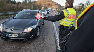 Des policiers allemands contrôlent un véhicule tentant de passer la frontière depuis la Moselle, à Sarrebruck (Allemagne), le 16 mars 2020, lors du premier confinement lié au Covid-19. (OLIVER DIETZE / DPA / AFP)