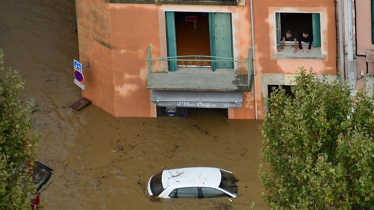 A Trèbes (Aude), une voiture est noyée dans une rue inondée, dans les intempéries du 15 octobre 2018. (SYLVAIN THOMAS / AFP)