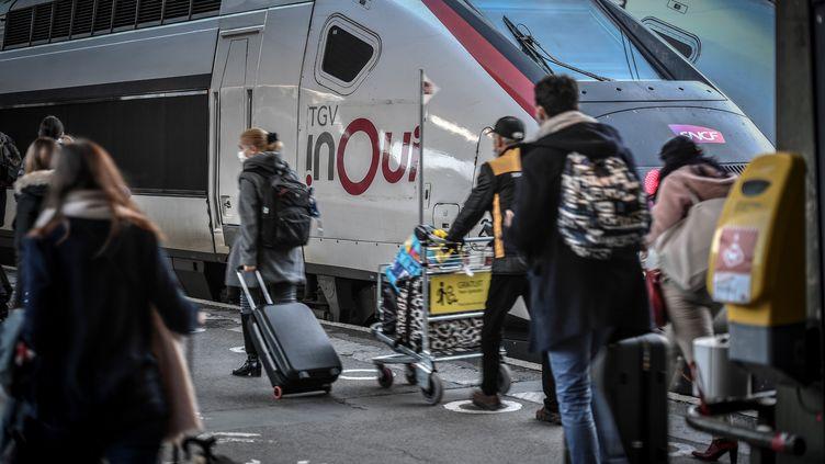 Des voyageurs marchent sur le quai de la Gare de Lyon avec leurs valises, en décembre 2020. (STEPHANE DE SAKUTIN / AFP)