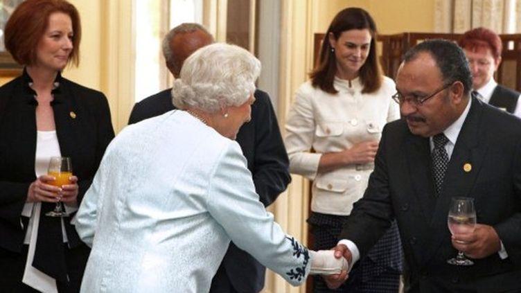 La reine d'Angleterre salue Peter O'Neill, président de Papouasie-Nouvelle-Guinée, avant le lancement de la réunion. (AFP PHOTO / POOL / COLIN MURTY)