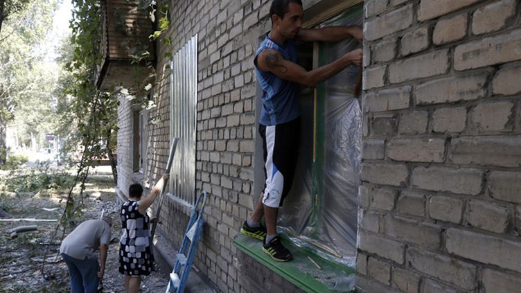 (Samedi à Donetsk, des habitants tentent de protéger leurs maisons avec des tôles de fer © REUTERS / Sergei Karpukhin)