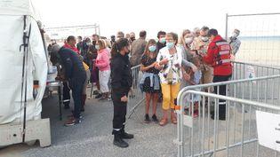 Des vacanciers portent le masque avant d'assister à un concert sur la plage du Canet-en-Roussillon, dans les Pyrénées-Orientales, le 13 juillet 2021. (SANDRINE ETOA-ANDEGUE / RADIO FRANCE)