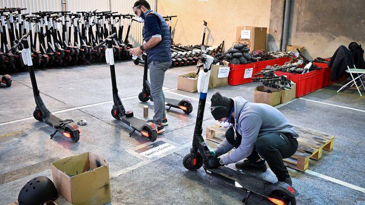 Des employés travaillent sur des trottinettes électriques à Marseille, le 18 novembre 2019. (GERARD JULIEN / AFP)