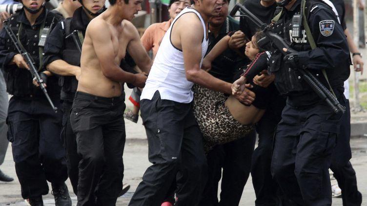 """Région autonome ouighoure du Xinjiang : le 7 juillet 2009, la police chinoise arrête plus de 1400 """"suspects"""" liés à des émeutes qui ont fait 156 morts et 800 blessés dans la capitale régionale Urumchi. (CHINA DAILY CDIC / X01745)"""