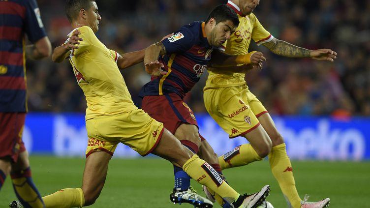 Luis Suarez (Barcelone) tente le passage en force entre deux défenseurs de Gijon (LLUIS GENE / AFP)